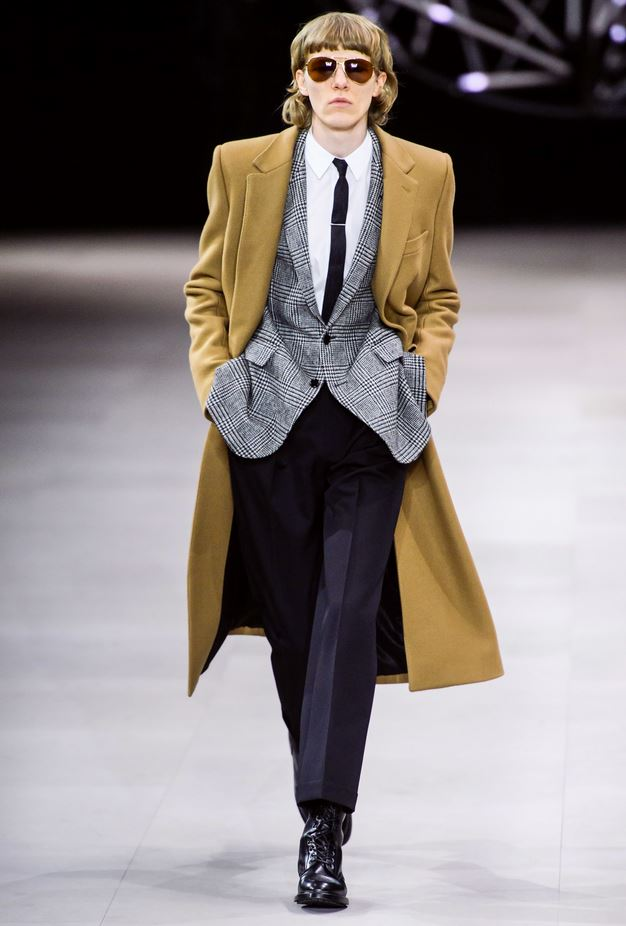 male model walking down runway with hands in pockets wearing Celine camel pea-coat, plaid blazer, white button down shirt, skinny black tie, black pants, black dress shoes, and aviator sunglasses.