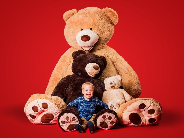 smiling child with giant teddy bears