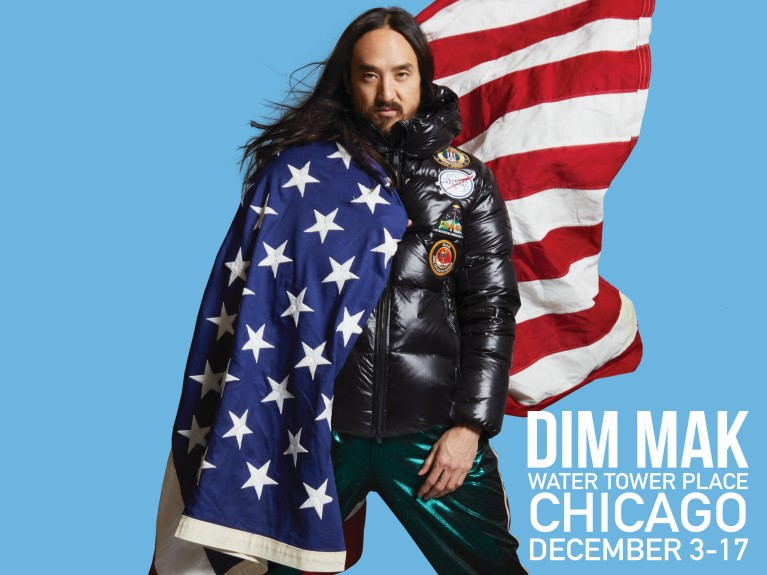 DJ, Steve Aoki, wrapped in American flag wearing black jacket from collection