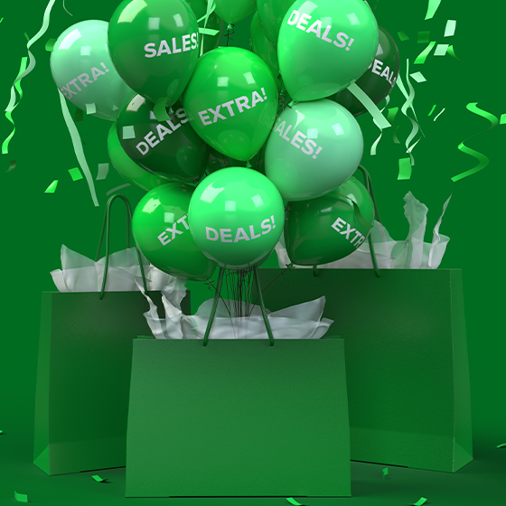 green balloons coming out of a shopping bag with confetti falling around