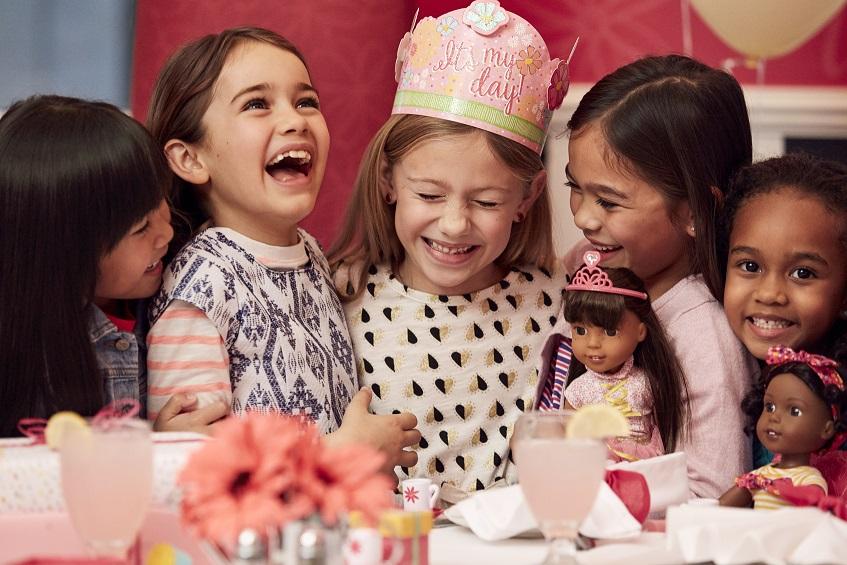 Girls celebrating birthday with dolls