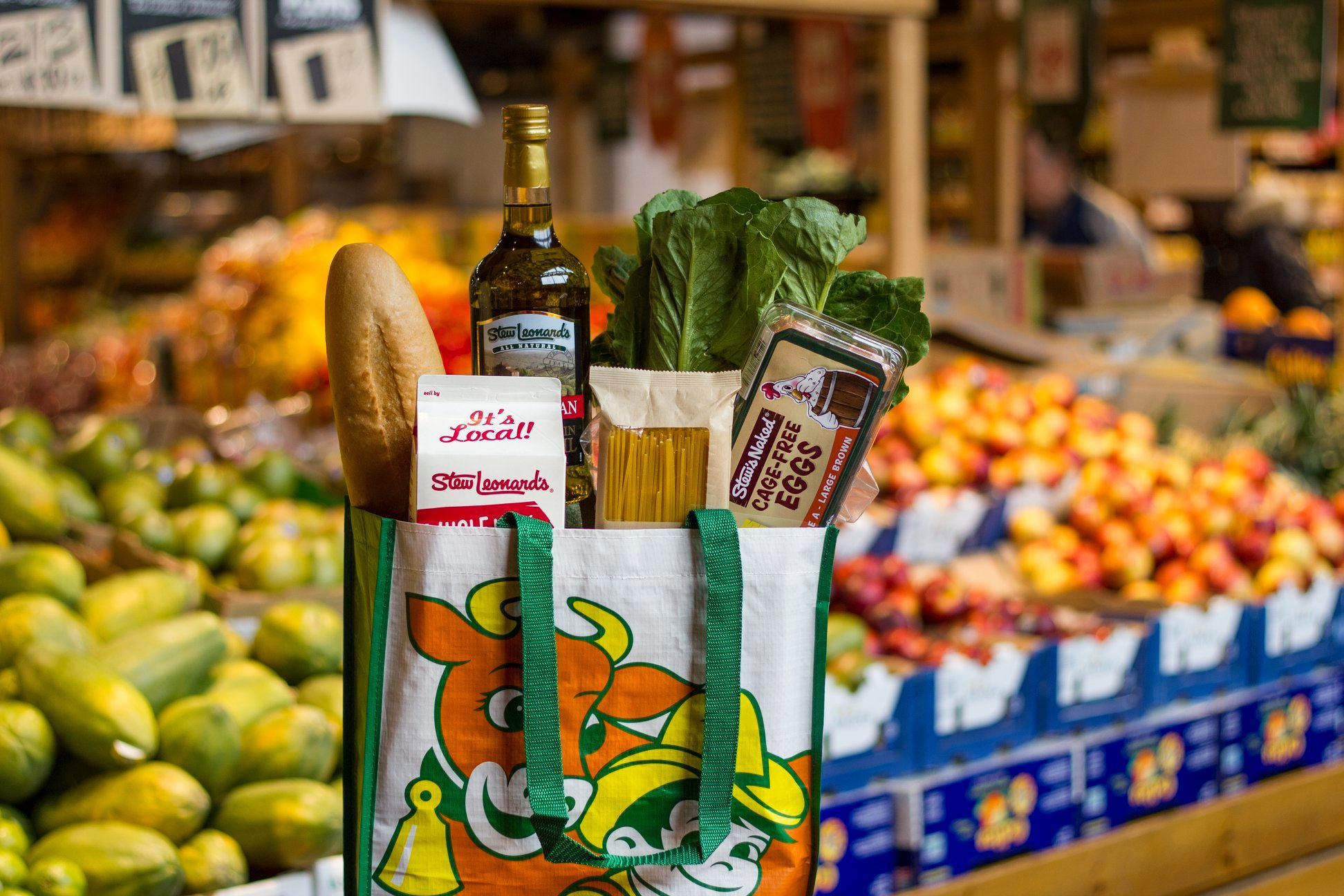 A grocery bag filled with bread, lettuce, pasta, milk, and eggs in front of a colorful produce stand.
