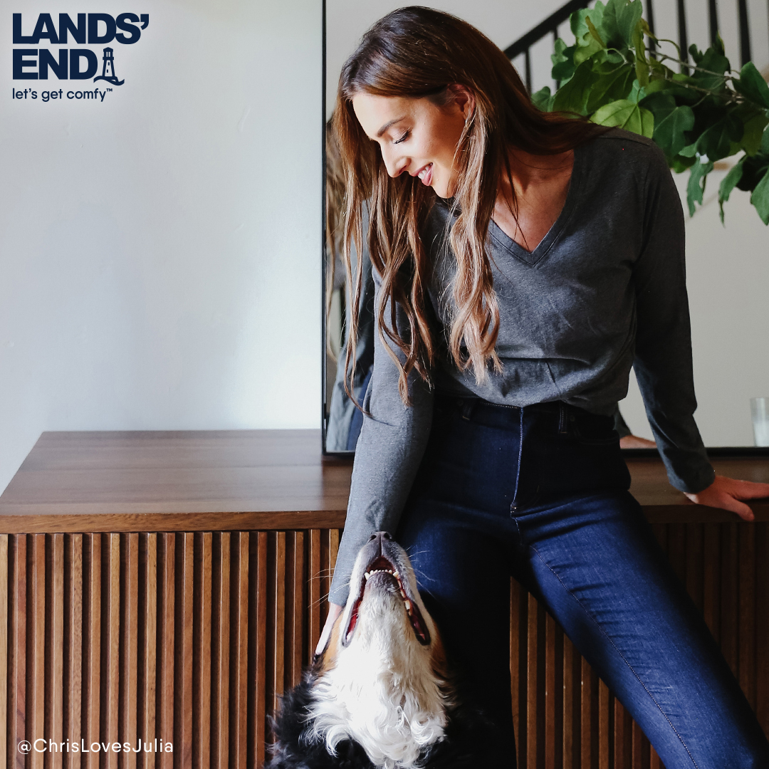 Female sitting on wooden bench in gray top and jeans, petting dog
