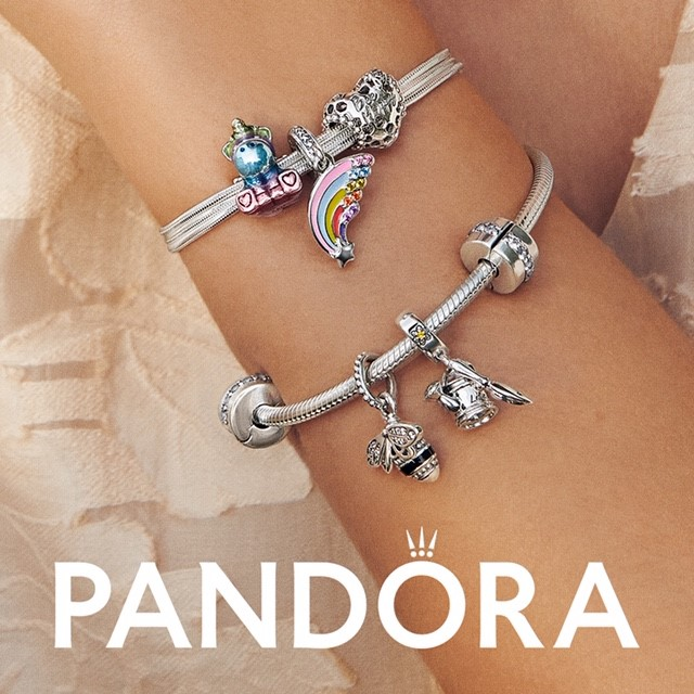 wrist with multiple Pandora bracelets on it