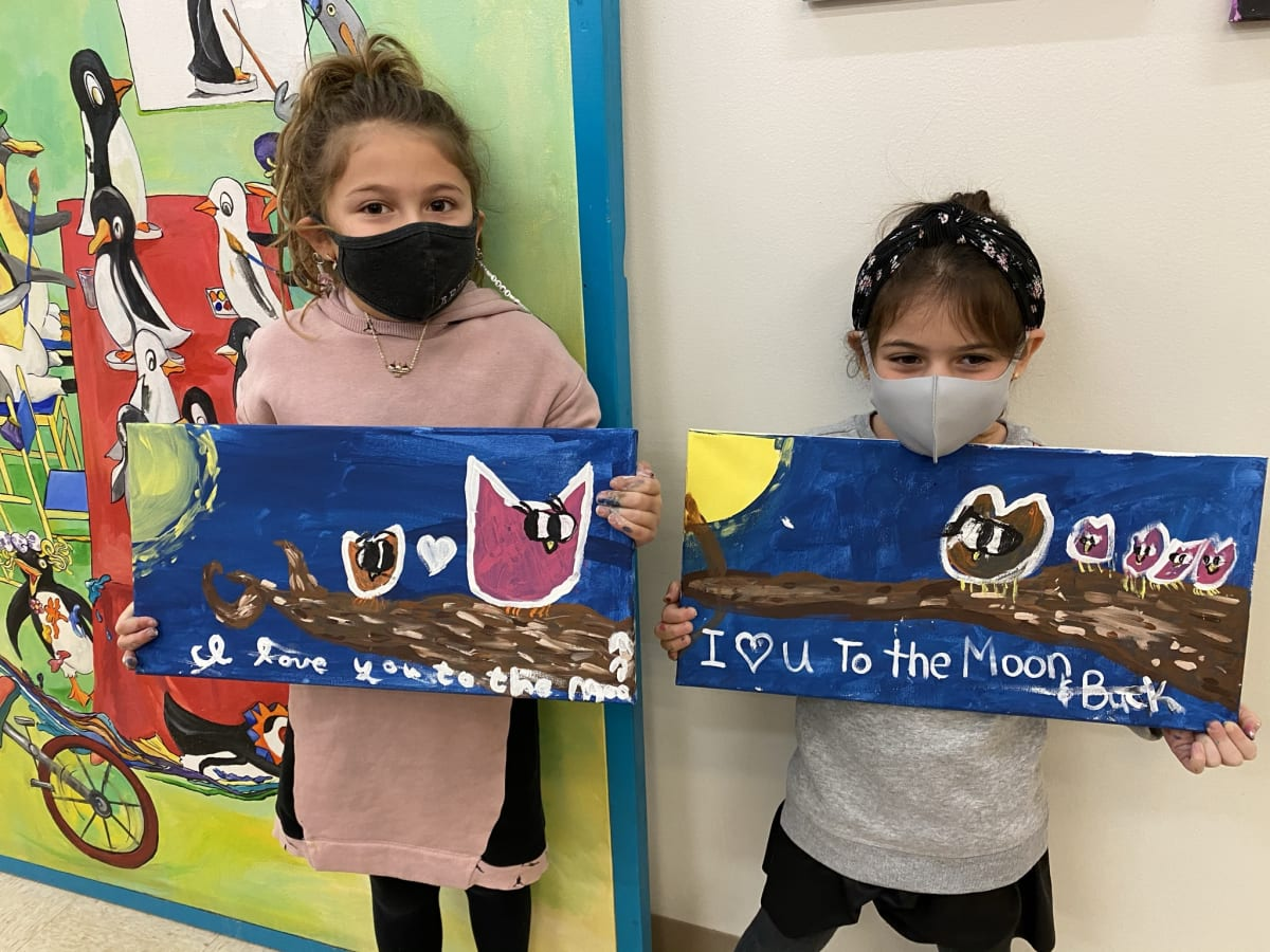 2 kids holding art they made in the summer art classes.