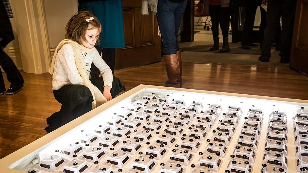 A young girl looking at Shohei Katayama's artwork, Proximity.